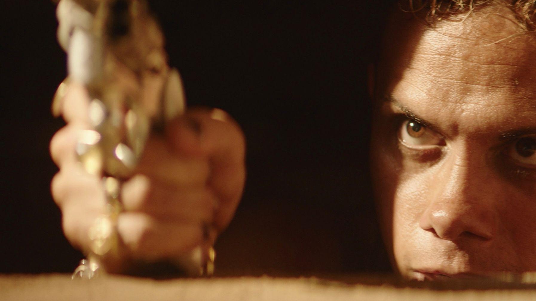 Filmszene aus von Kleber Mendonça Filho und Juliano Dornelles (Mann in extremer Nahsicht hält eine Waffe Richtung Kamera)