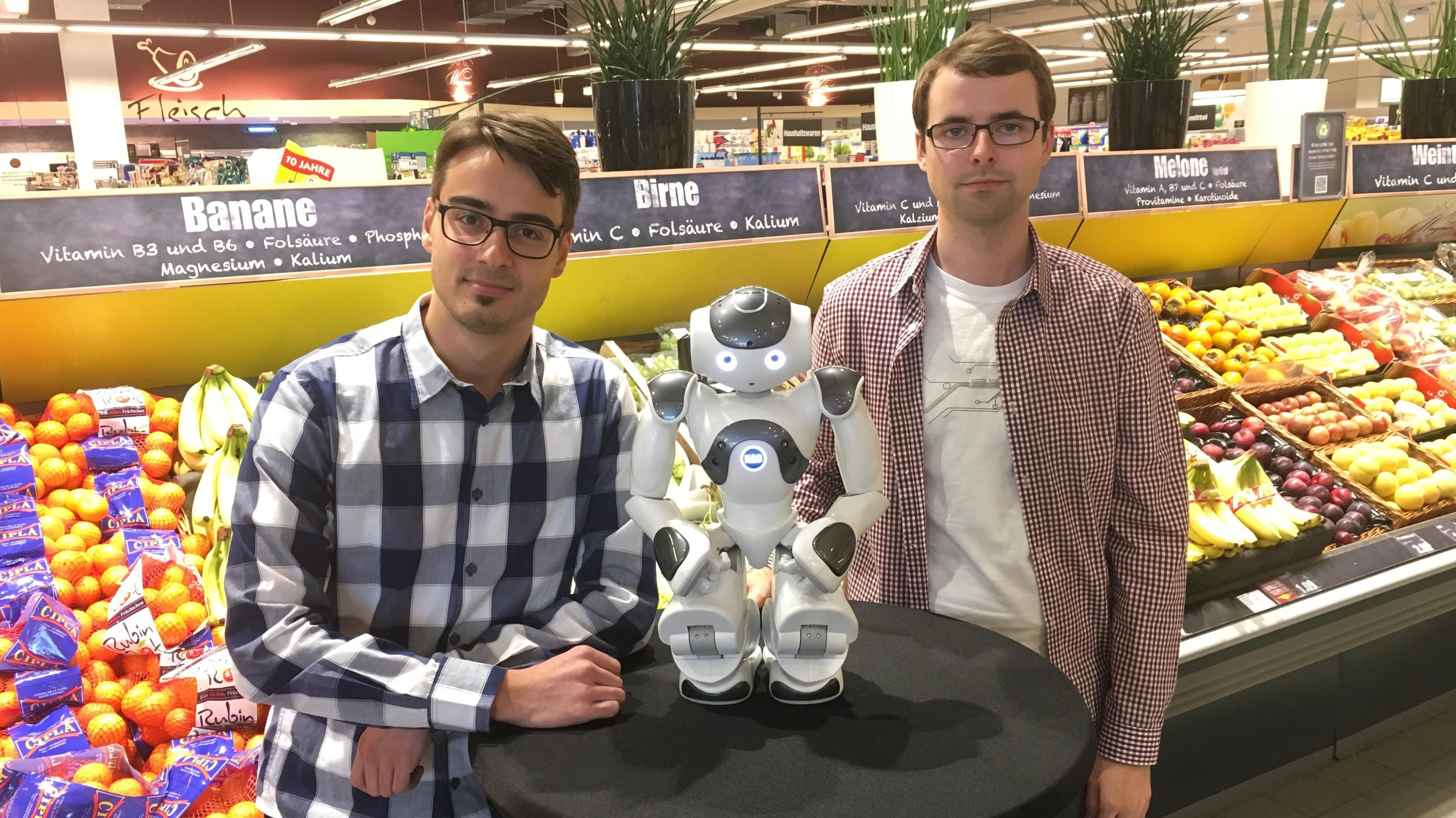 Zwischen zwei Männern steht in einem Supermarkt vor dem Obstregal ein kleiner weißer Roboter auf einem Hochtisch.