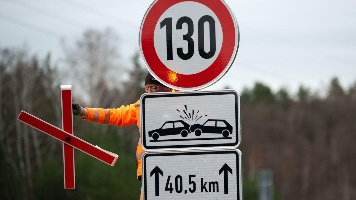 Ein Arbeiter entfernt auf der Autobahn A13 das Kreuz von dem Verkehrszeichen zur Geschwindigkeitsbegrenzung.