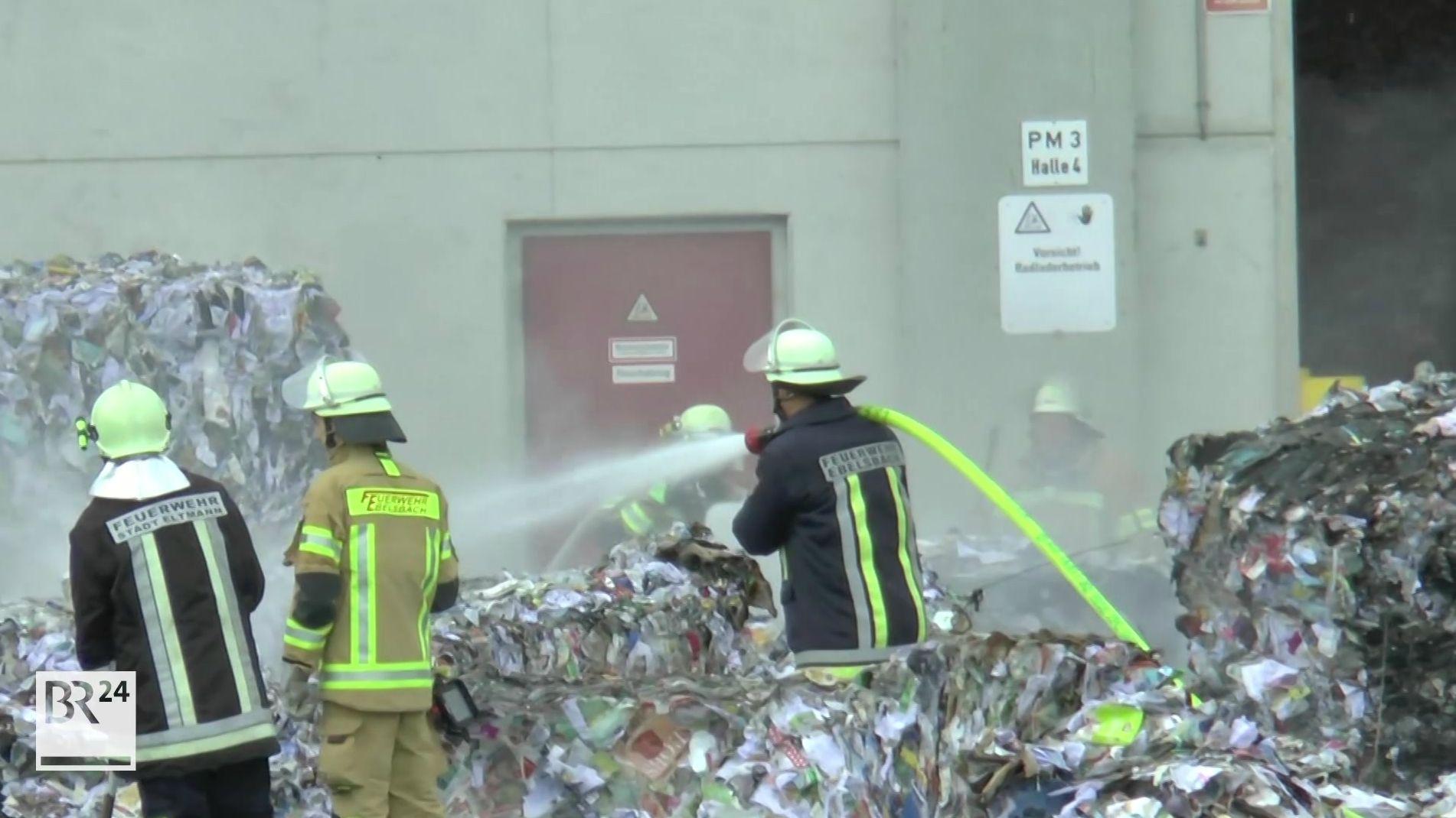 Feuerwehrmänner löschen einen Brand in einer Papierfabrik in Eltmann (Lkr. Haßberge).