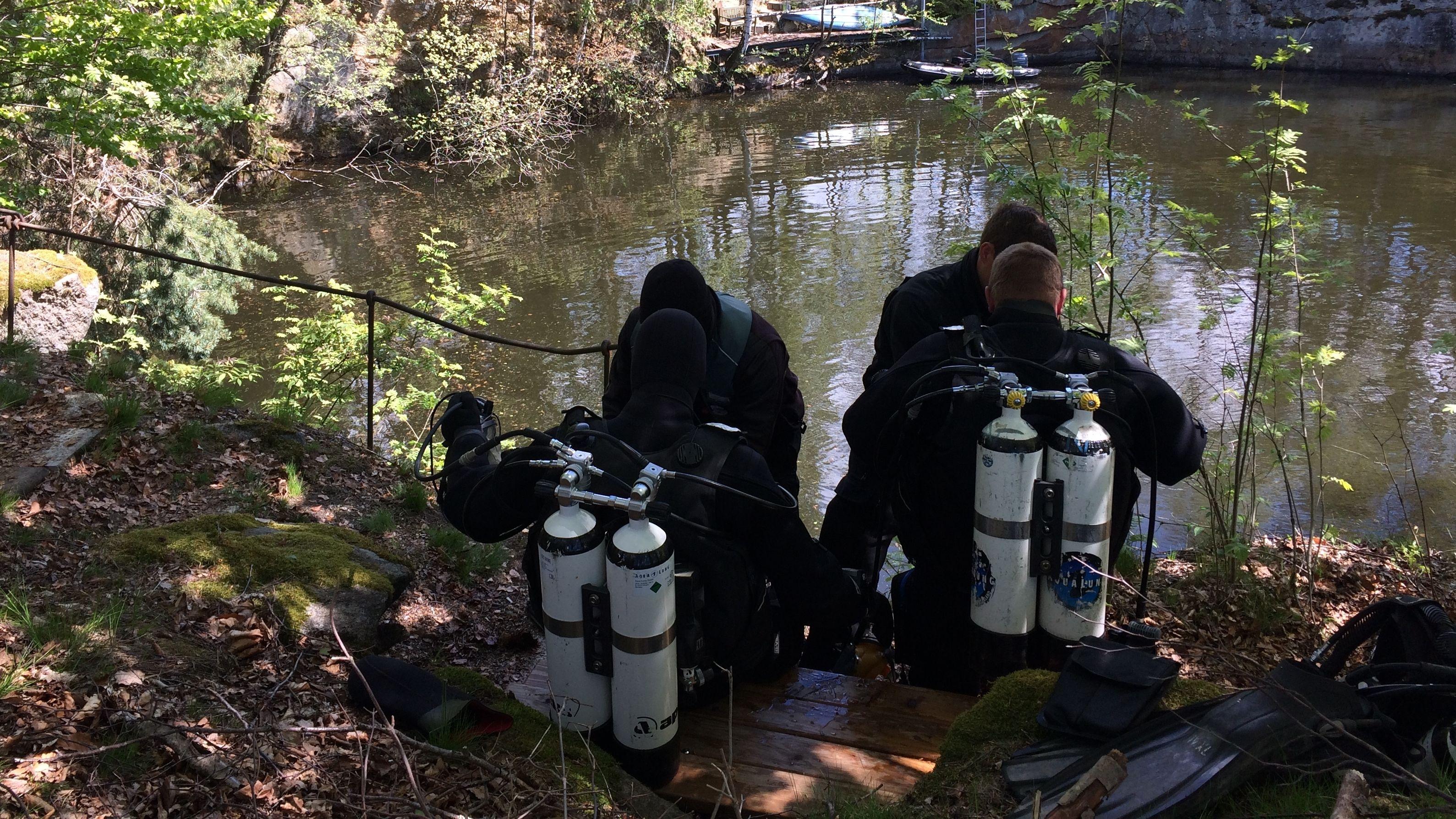 Vier Polizeitaucher am Ufer eines Weihers in der Ortschaft Waldkirch.