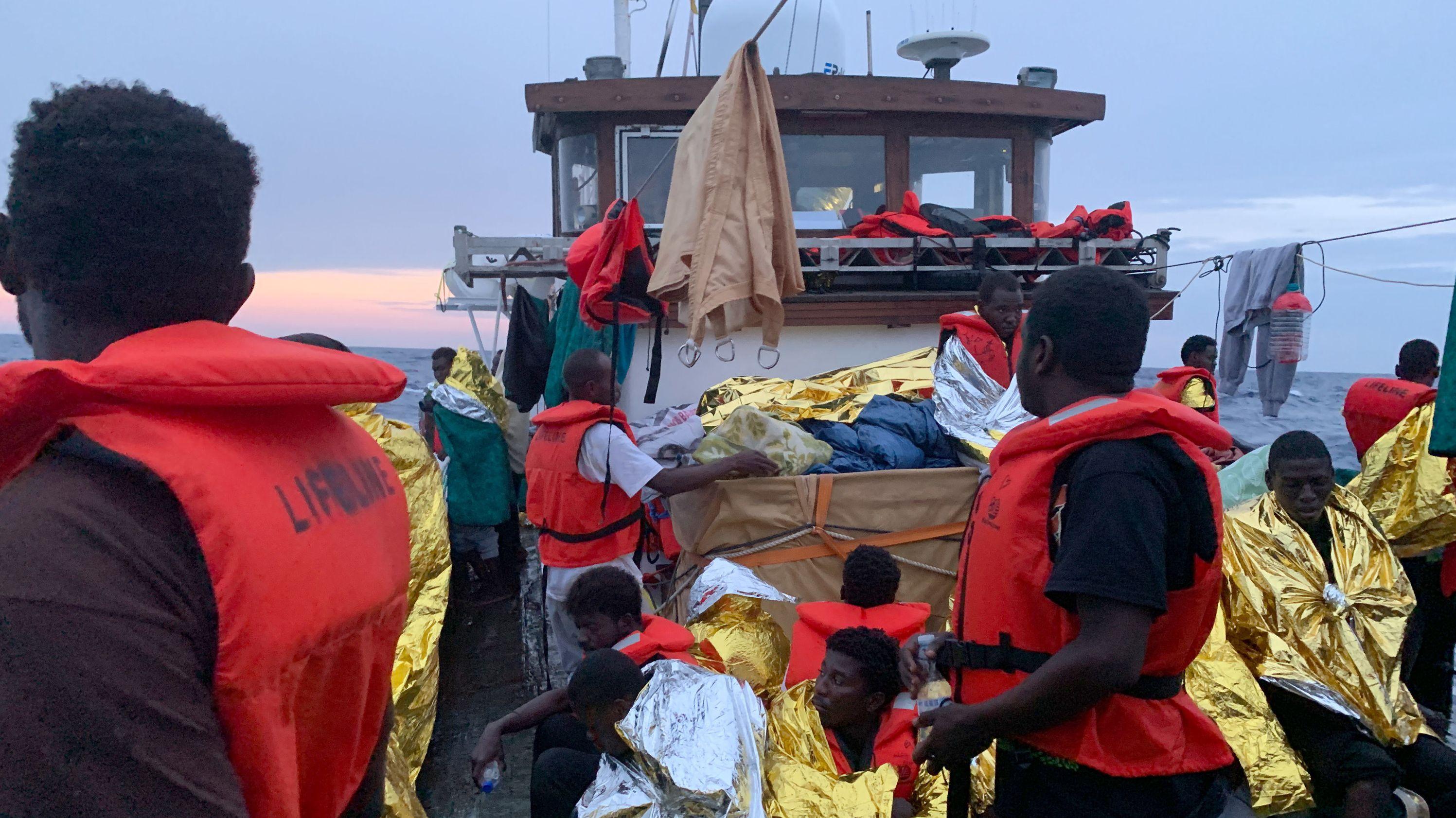 """Nach einem Gewitter mit schweren Regenfällen schützen sich die rund 100 Migranten an Deck des Rettungsschiff """"Eleonore"""" mit Rettungsdecken"""