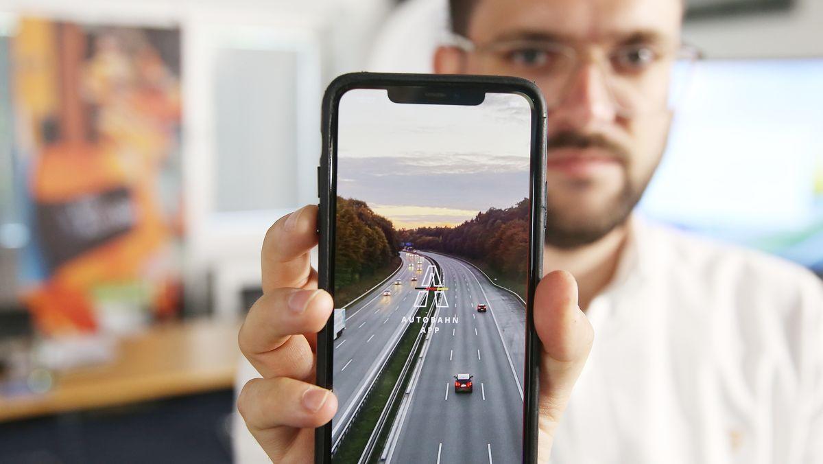 Philipp Plümicke von der Firma prototype.berlin app development & design zeigt bei einem Pressetermin auf seinem Smartphone die neue App der Autobahn GmbH des Bundes.