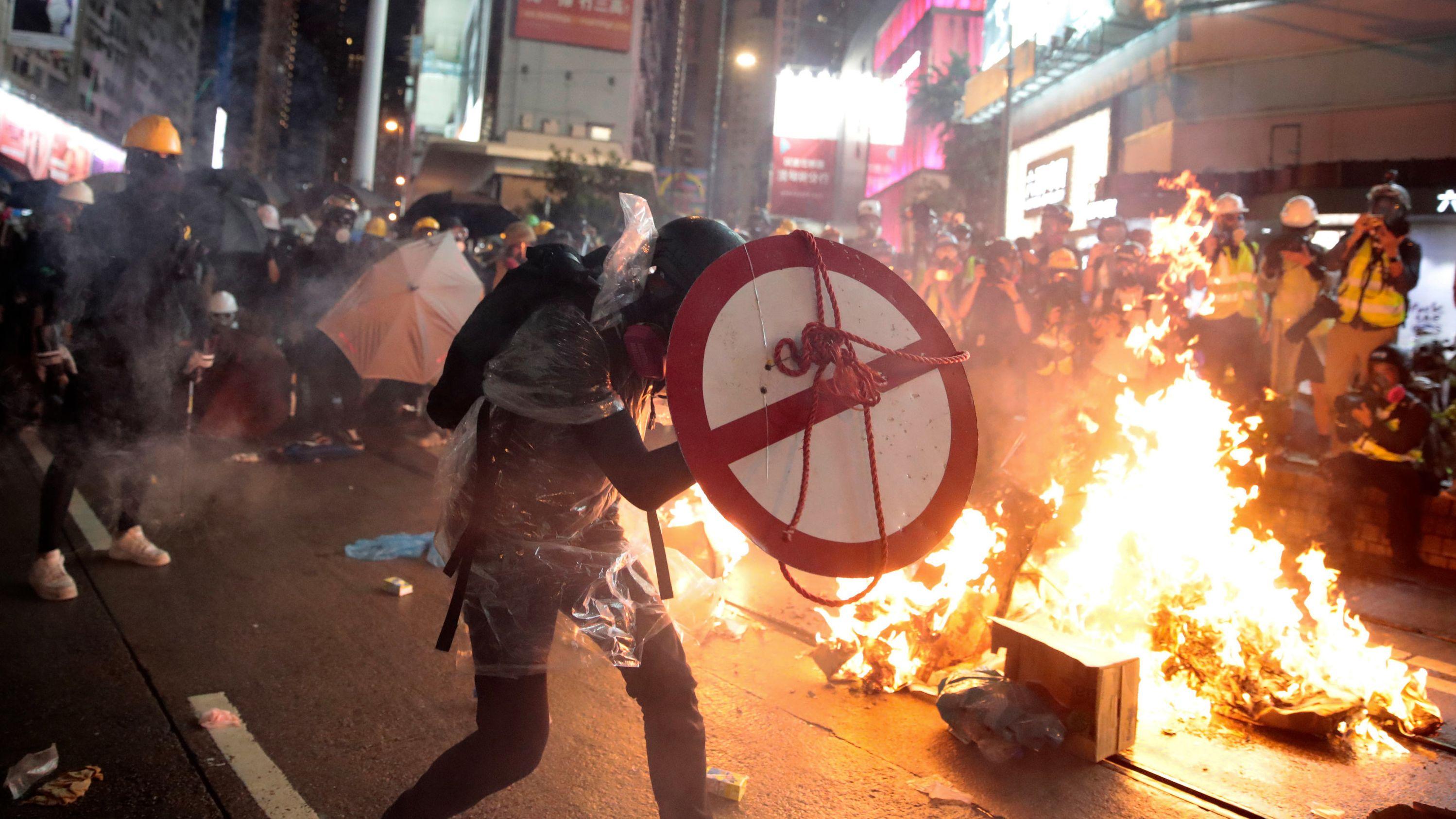 Ein Demonstrant in Hongkong geht hinter einem Schild in Deckung, während im Hintergrund ein Feuer brennt.