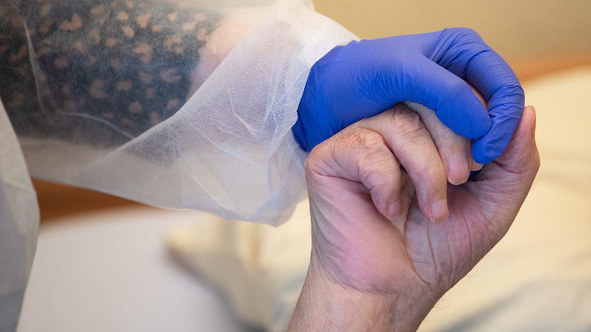 Pflegerin in Schutzkleidung hält die Hand eines Bewohners