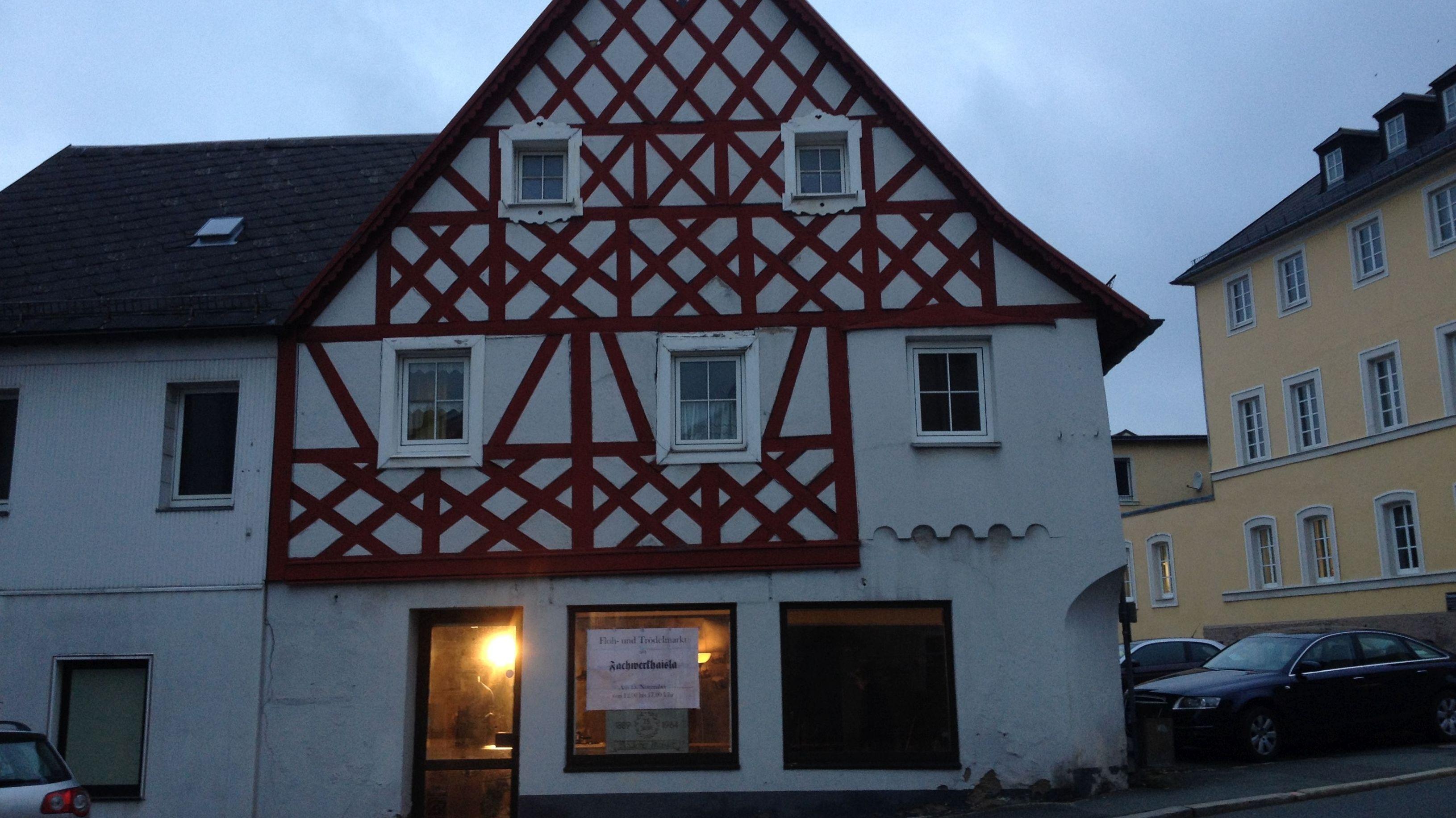 Ein altes, sanierungsbedürftiges Fachwerkhaus in Münchberg, davor und daneben Autos