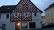 Ein altes, sanierungsbedürftiges Fachwerkhaus in Münchberg, davor und daneben Autos   Bild:BR/Annerose Zuber