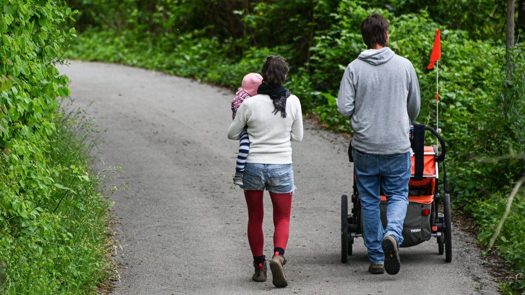 Ein Paar mit Kind läuft eine schmale Straße entlang, die auf beiden Seiten bewachsen ist.