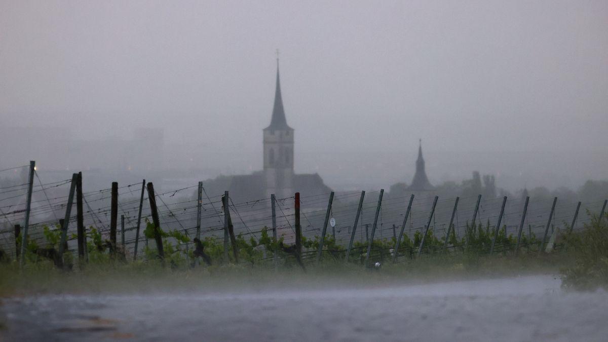 Im Starkregen liegen die Weinberge am Schwanberg vor dem Kirchturm des Ortes.