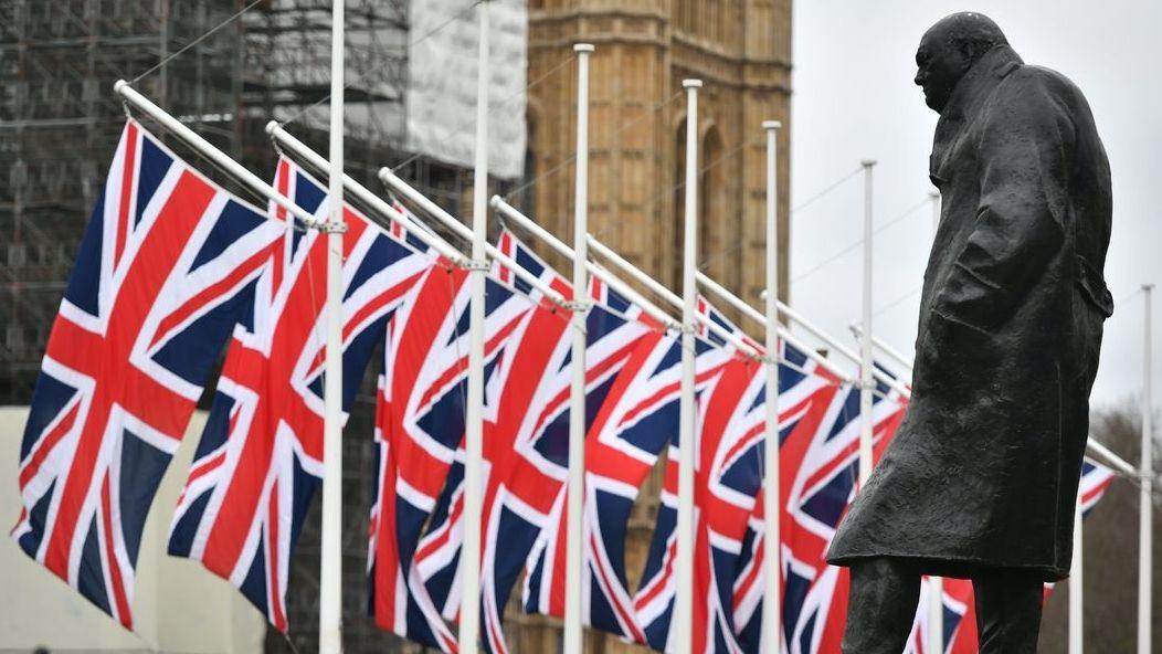 London: Die Winston-Churchill-Statue und die britischen Flaggen auf dem Parliament Square.
