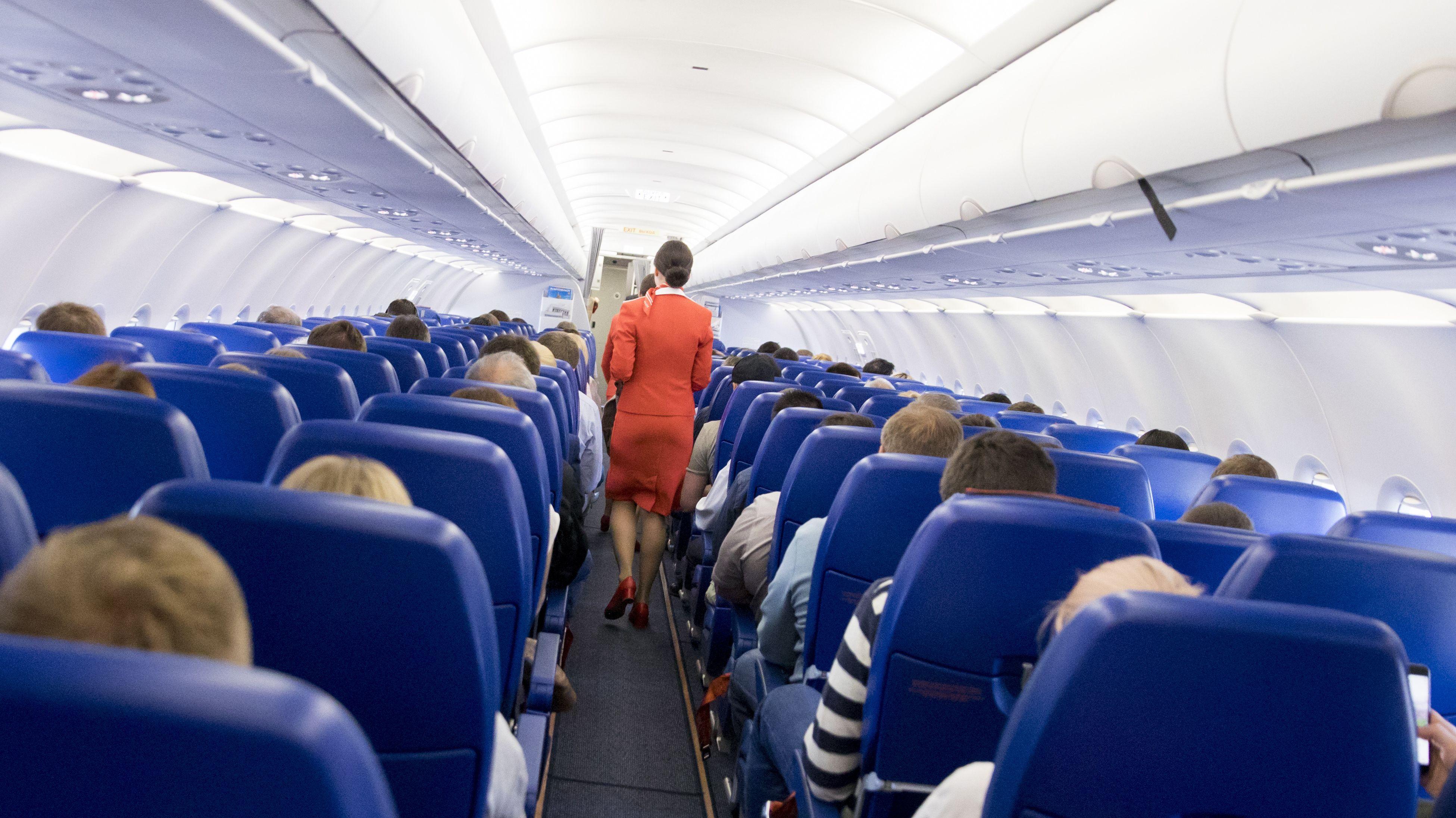 Flugbegleiterinnen verteilen Getränke an die Fluggäste.
