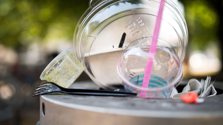 Plastikgeschirr und -besteck liegen auf einem Mülleimer.