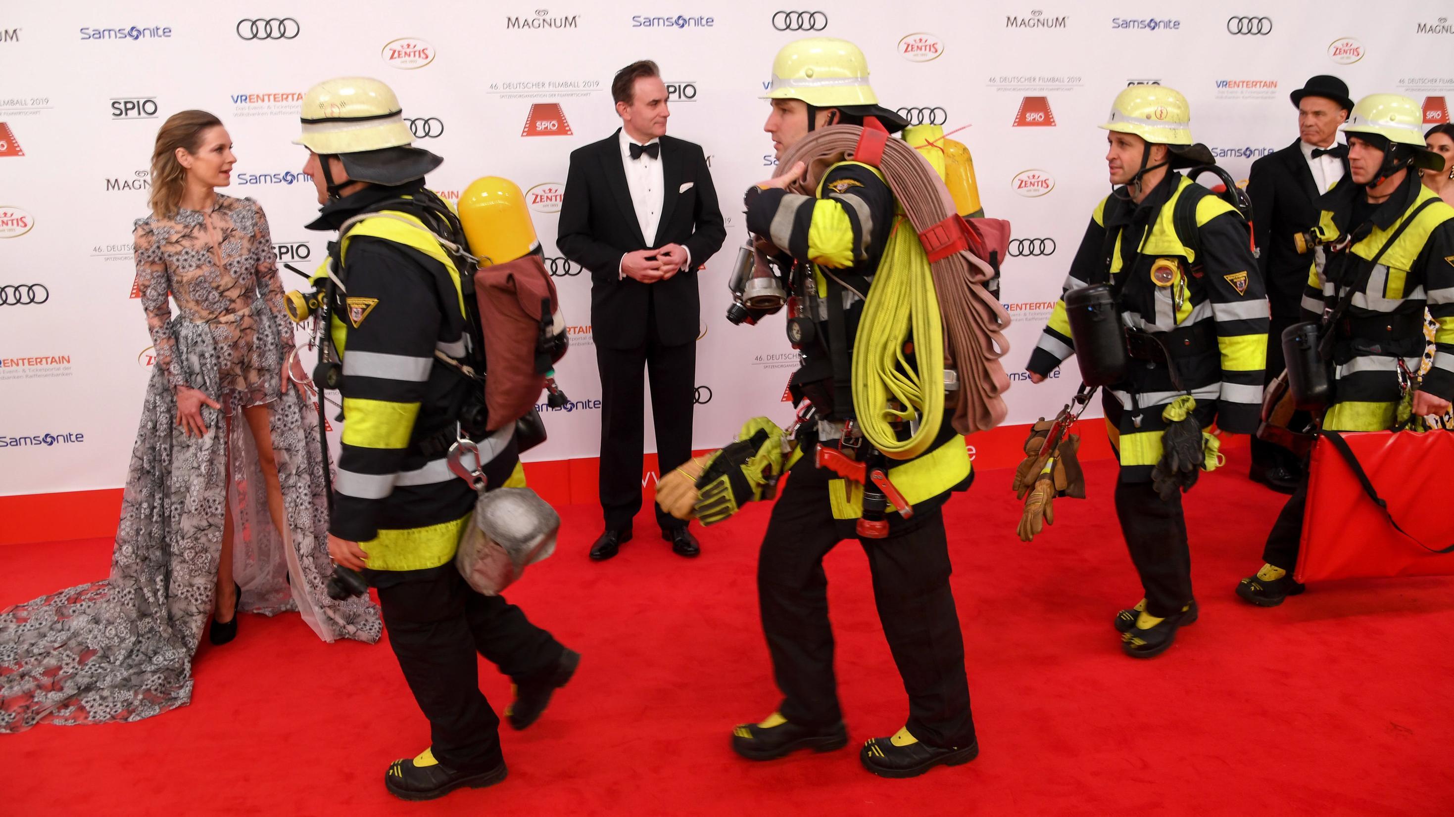 """Unter den Blicken von Schauspielerin Lisa Martinek und ihrem Mann Giulio Ricciarelli laufen Feuerwehrleute beim 46. Deutscher Filmball 2019 über den roten Teppich ins Hotel """"Bayerischer Hof""""."""