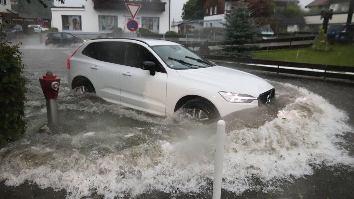 Auto fährt durch das hoch stehende Wasser auf einer Straße im Landkreis Oberallgäu