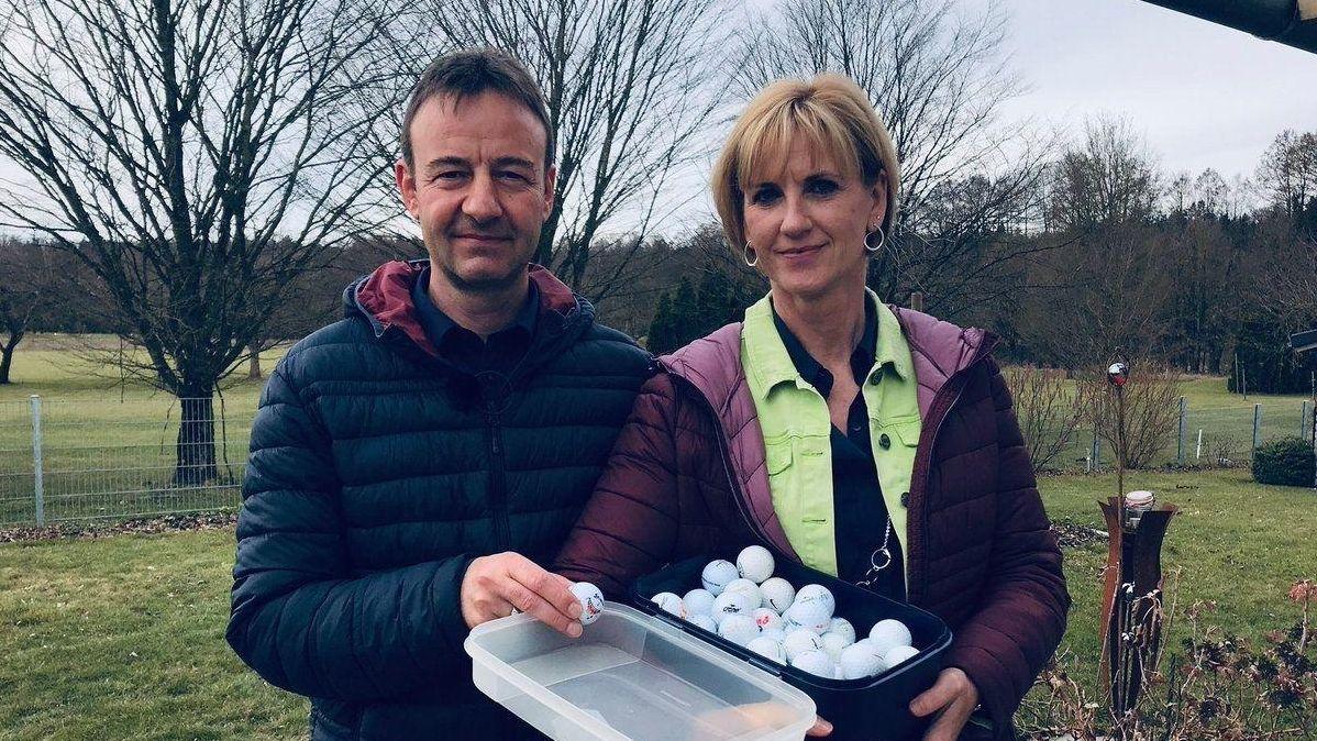 Christian und Birgit Koller halten eine Box mit Golfbällen, die auf ihr Grundstück geflogen sind.