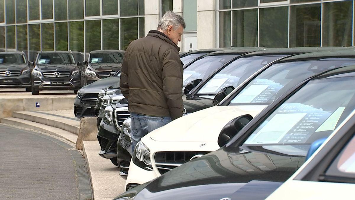 Ein Mann sieht sich die Preisschilder bei Autos an