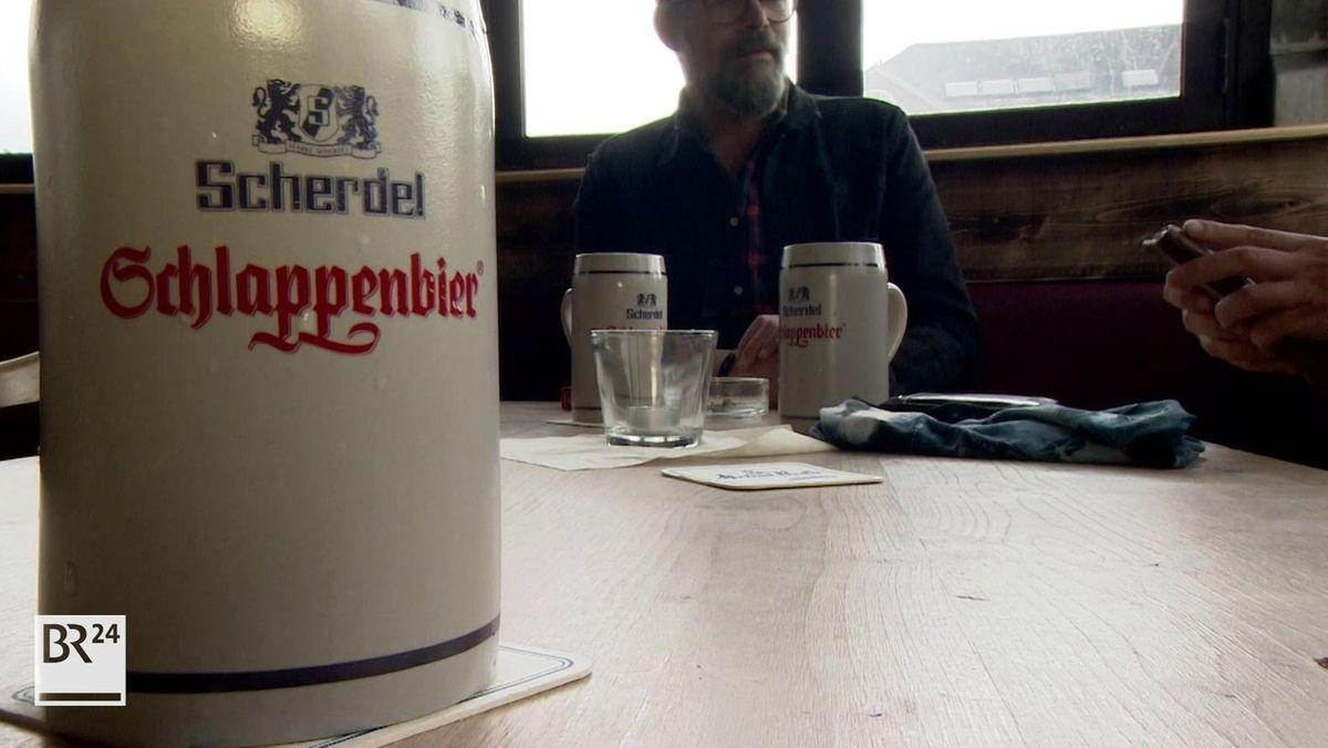 """Ein Maßkrug mit der Aufschrift """"Schlappentag"""" in roter Schrift steht auf einem Tisch, dahinter ein Mann."""