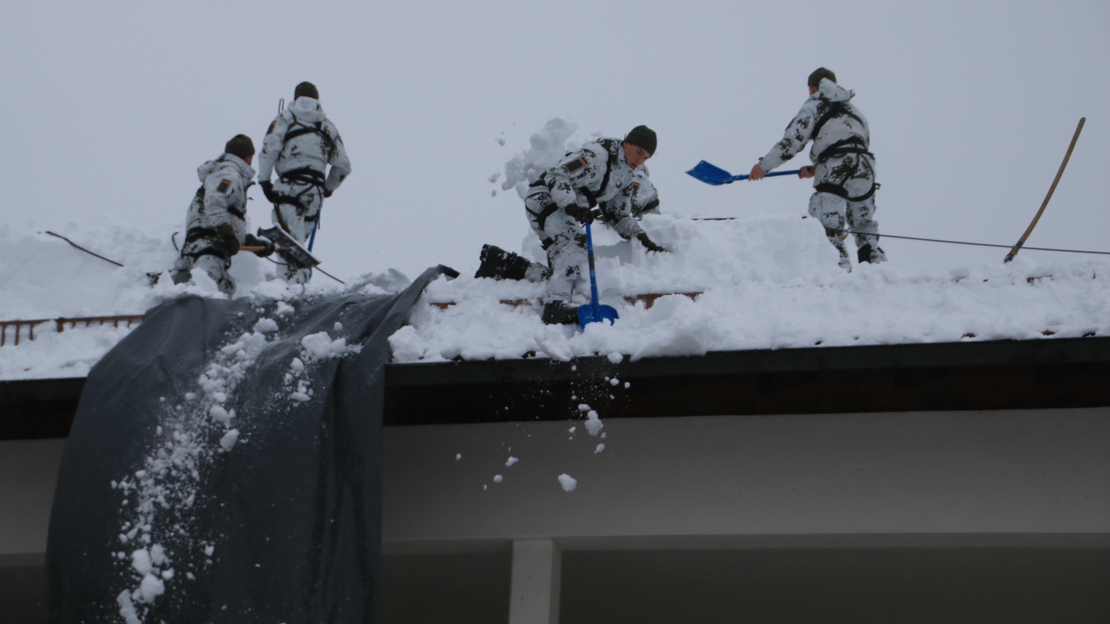 Soldaten des Gebirgsjägerbataillons 233 befreien ein Dach vom Schnee in Bad Heilbrunn im Landkreis Bad Tölz-Wolfratshausen.
