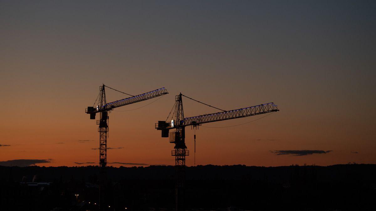Zwei Kräne stehen vor dem Abendhimmel auf einer Baustelle.