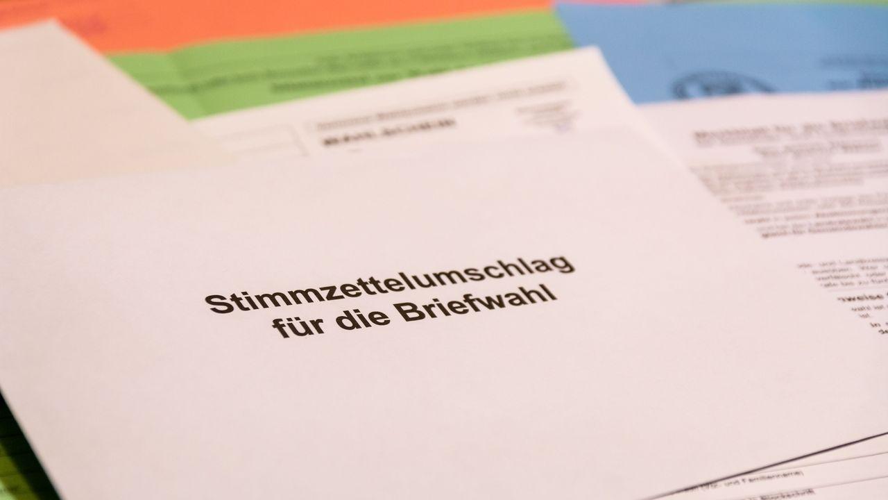 Ein Stimmzettelumschlag für die Kommunalwahl 2020, im Hintergrund Briefwahlunterlagen