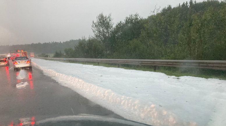 Eine dicke Schicht mit Hagelkörnern liegt nach den Unwettern vom Montagabend auf dem Randstreifen der Autobahn 8   Bild:pa/dpa/Jutta Steinhoff