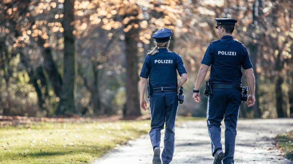 Ein Polizist und eine Polizistin gehen in einem Park auf Streife