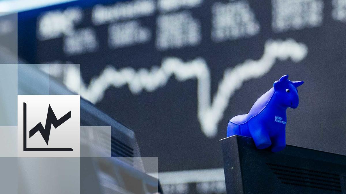 ein blauer Stier aus Gummi sitzt auf der oberen Kante eines Bildschirmes. Im Hintergrund die Kurstafel der Börse