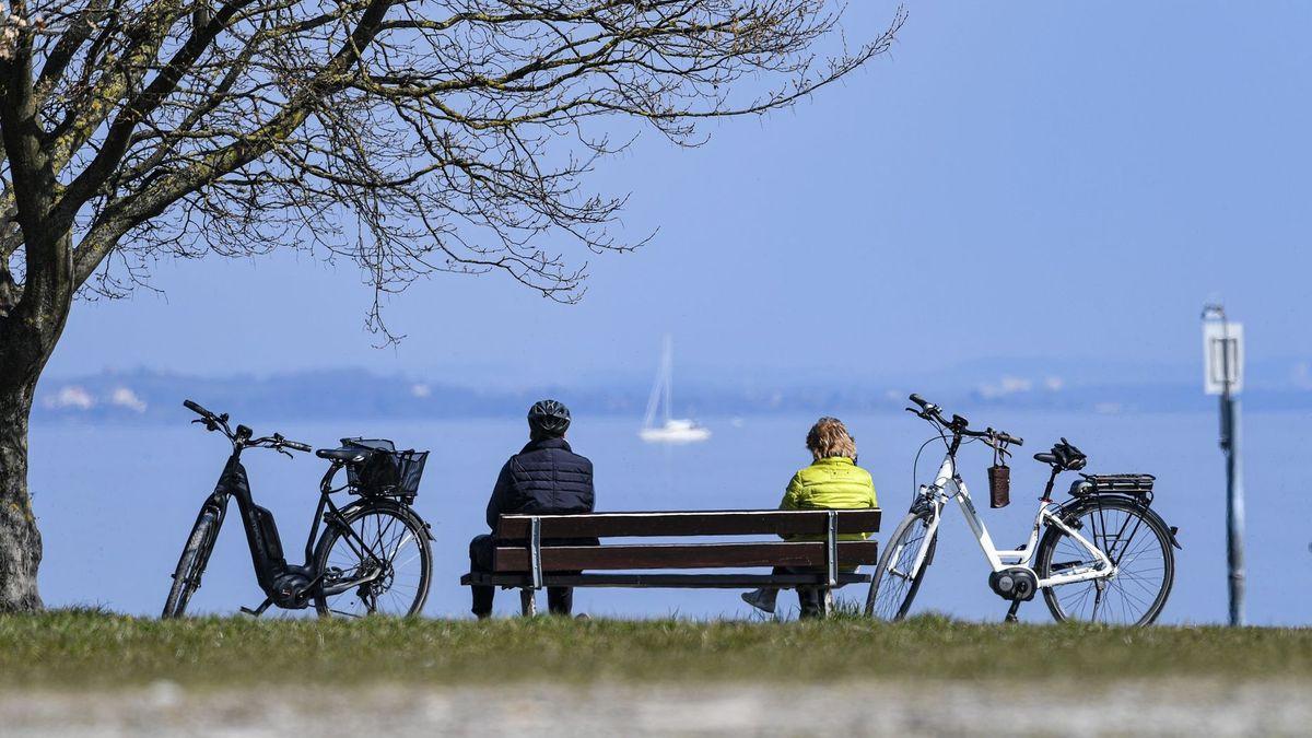 Zwei Menschen sitzen auf Abstand
