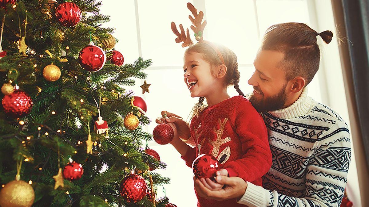 Vater und Tochter unter einem Weihnachtsbaum (Symbolbild)