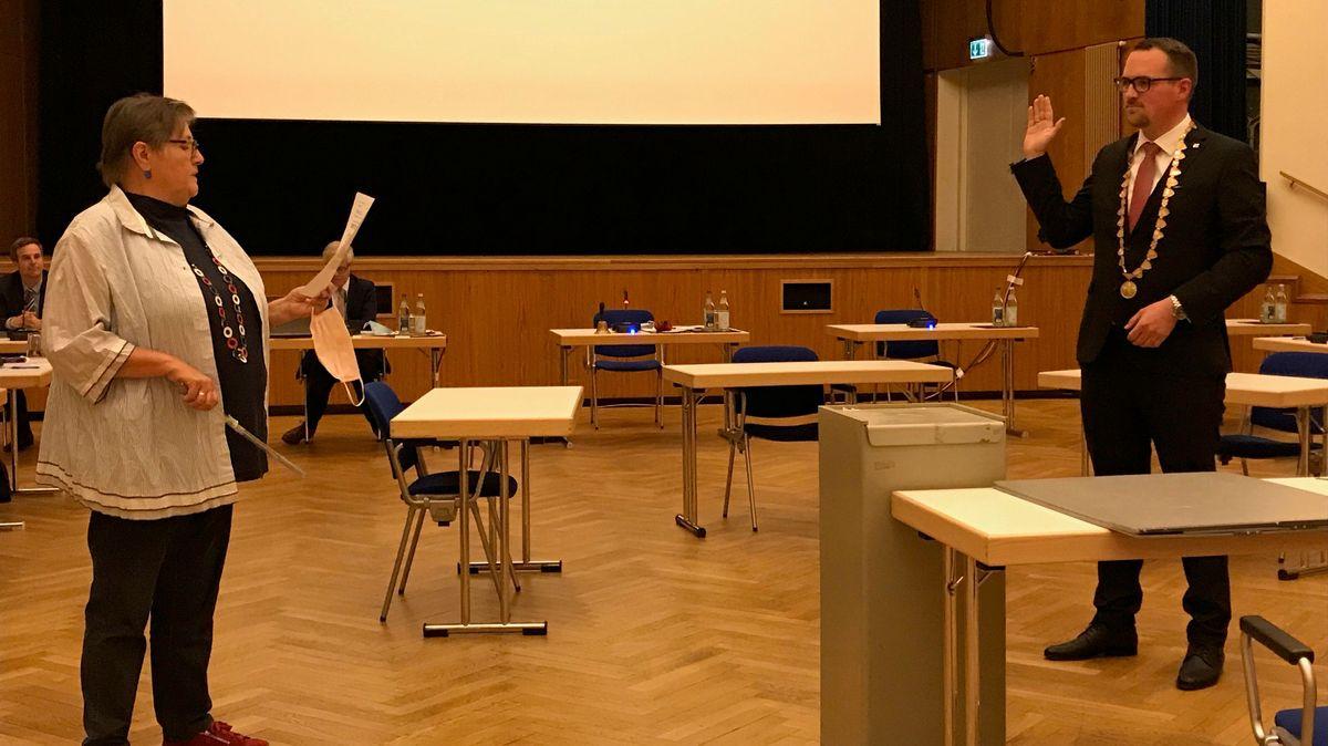 Bildunterschrift:Altbürgermeisterin Rosy Stengel (CSU) überreicht dem neuen OB Peter Reiß nach der Vereidigung einen Dirigentenstab.