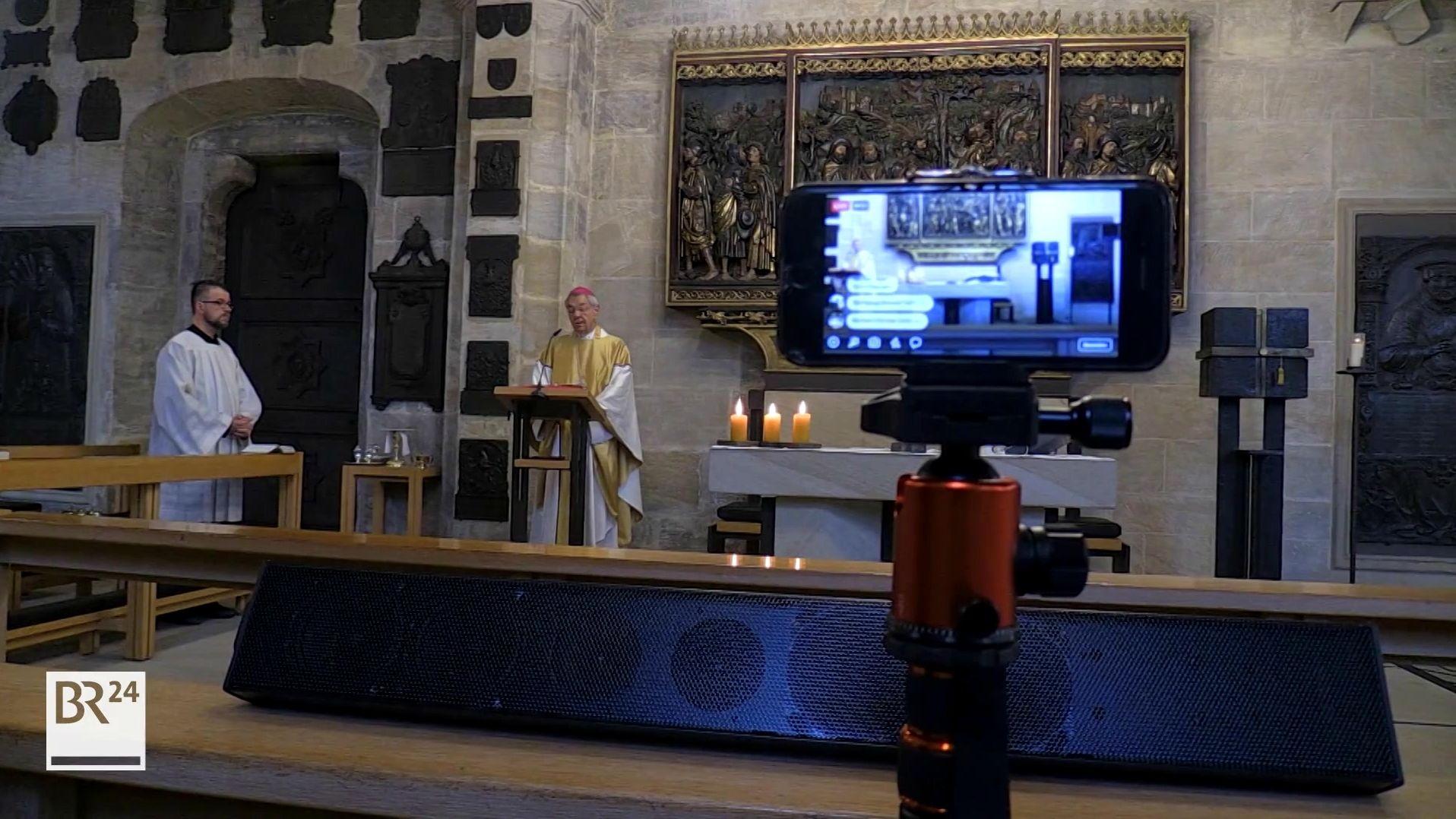 Der Bamberger Erzbischof Ludwig Schick steht am Altar, eine Videokamera zeichnet den Gottesdienst auf.