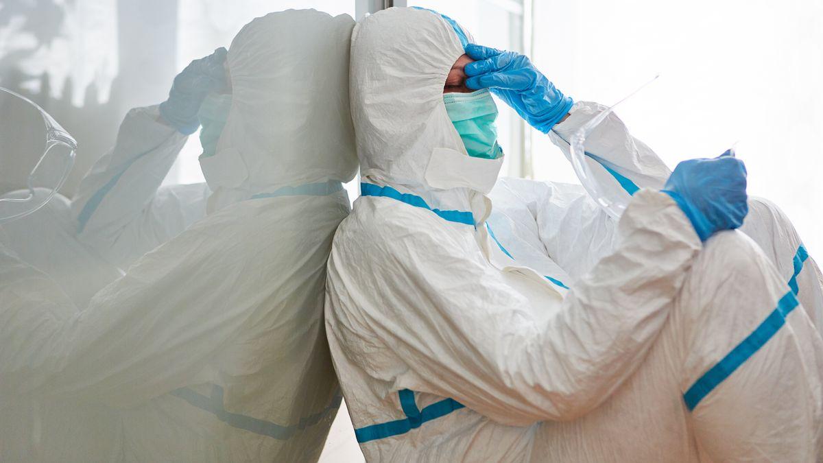 In einem Krankenhaus: Eine erschöpfte Mitarbeiterin in einem Schutzanzug