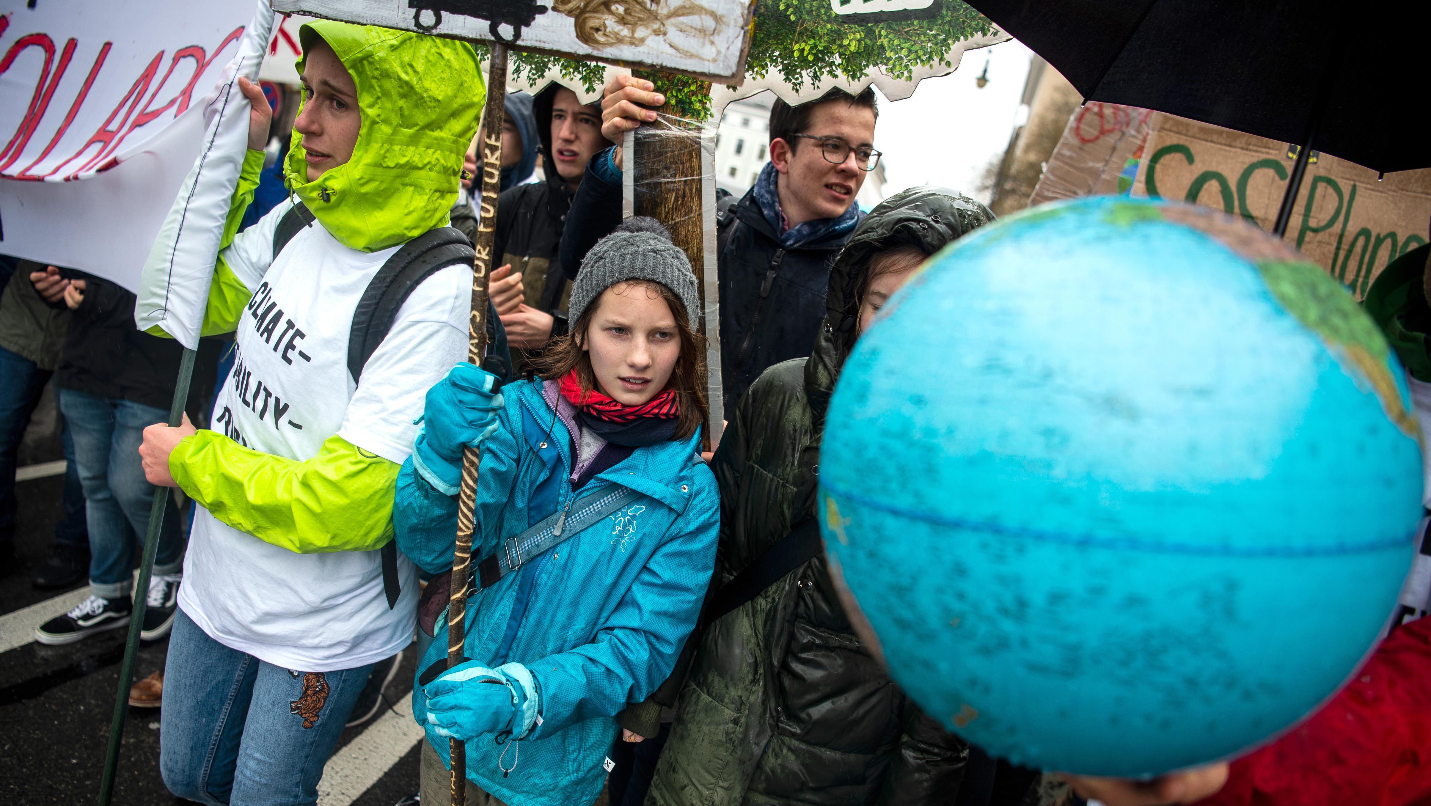 """Schüler beteiligen sich an der """"Fridays for Future""""-Klimademonstration, sie tragen Transparente und eine Weltkugel"""