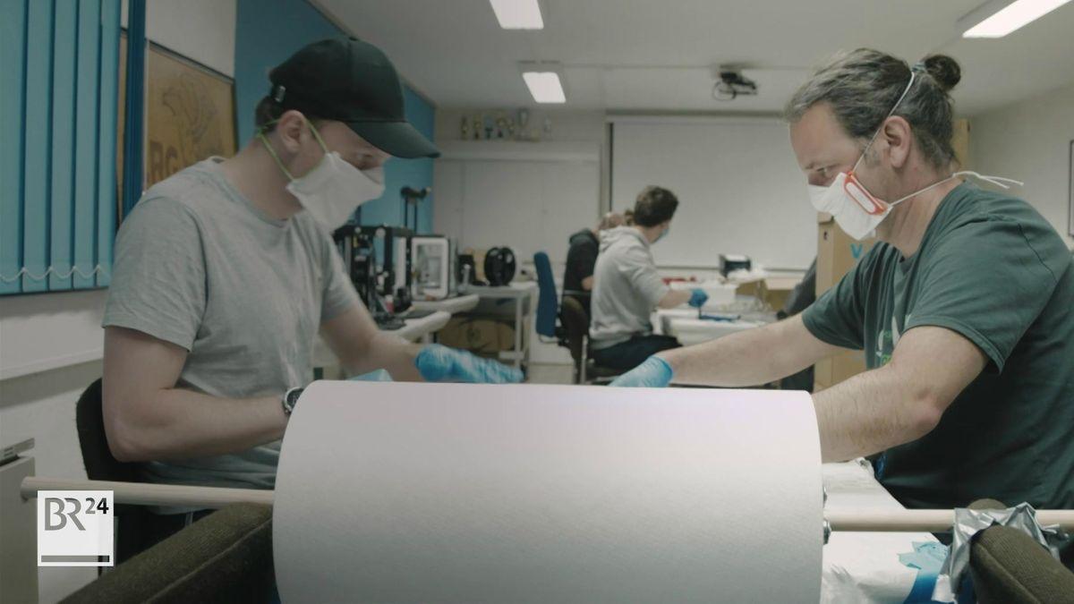 Zwei Maker schneiden Stoff für Mundschutz