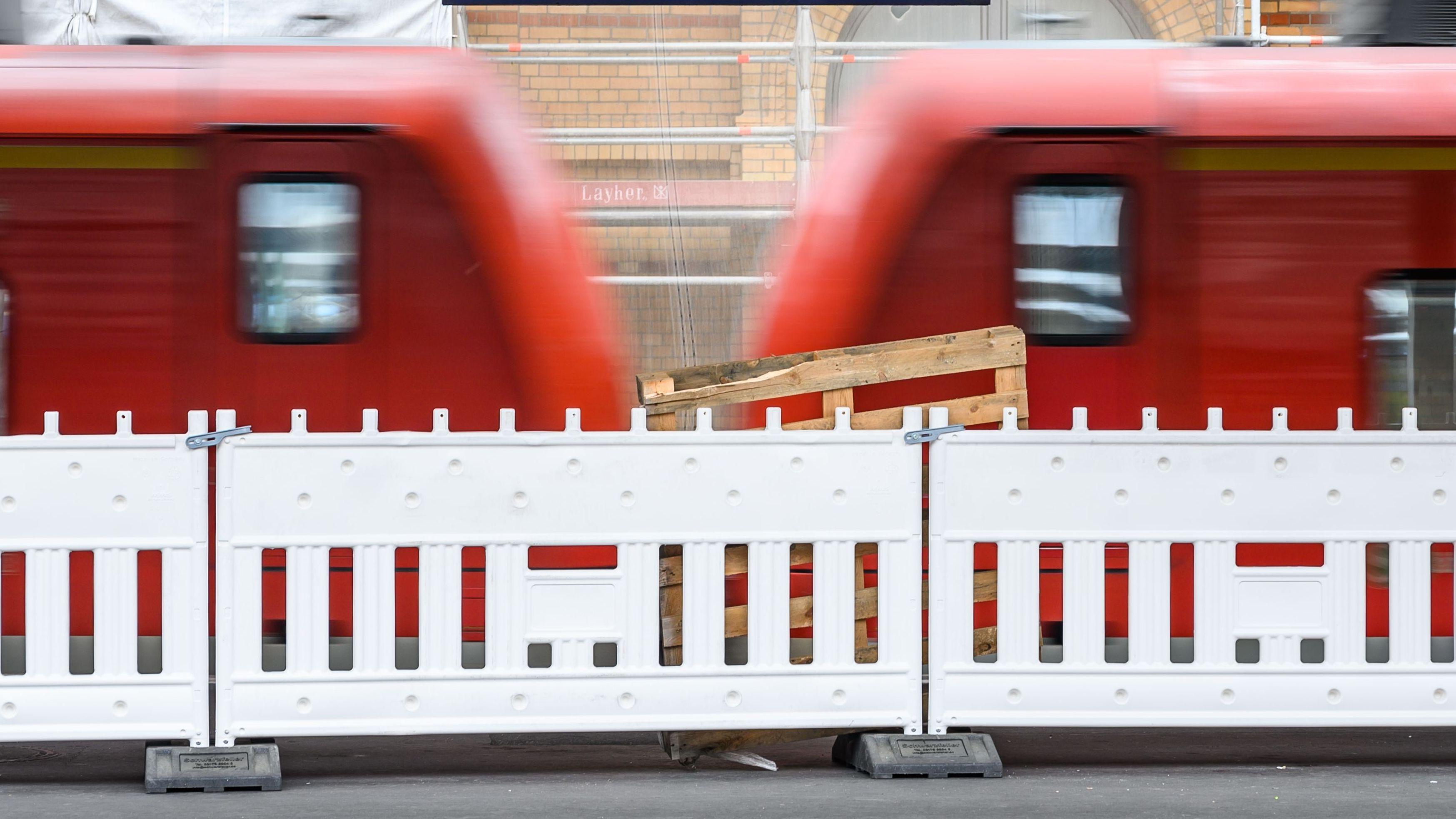 Ein Zug der Deutschen Bahn fährt vor Bauabsperrungen in einen Bahnhof ein