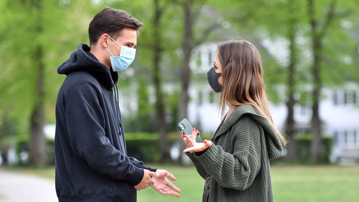 Ein Mann und eine Frau stehen sich mit Mundschutz gegenüber