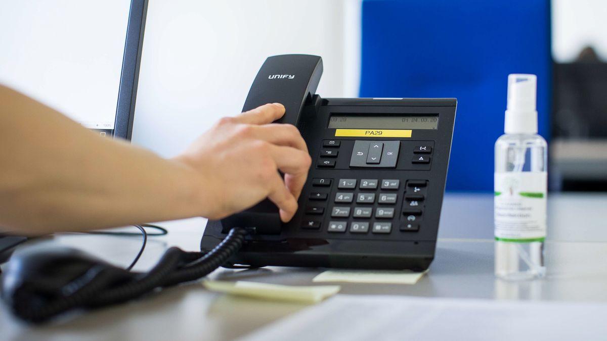 Mitarbeiter einer Hotline hat den Telefonhörer in der Hand.