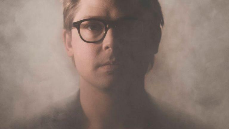 Otis Sandsjö , ein blonder Mann mit schwarzer Hornbrille blickt frontal in die Kamera.