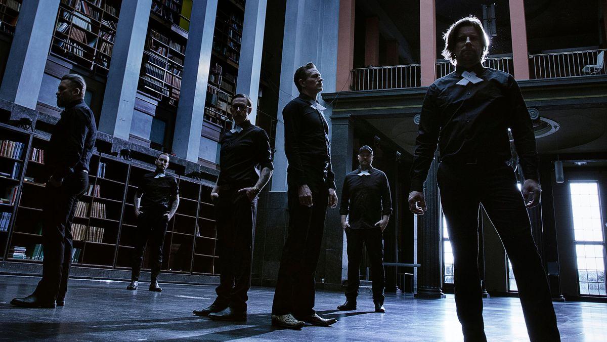 Männer in schwarzen Anzügen stehen in einem langen Raum.