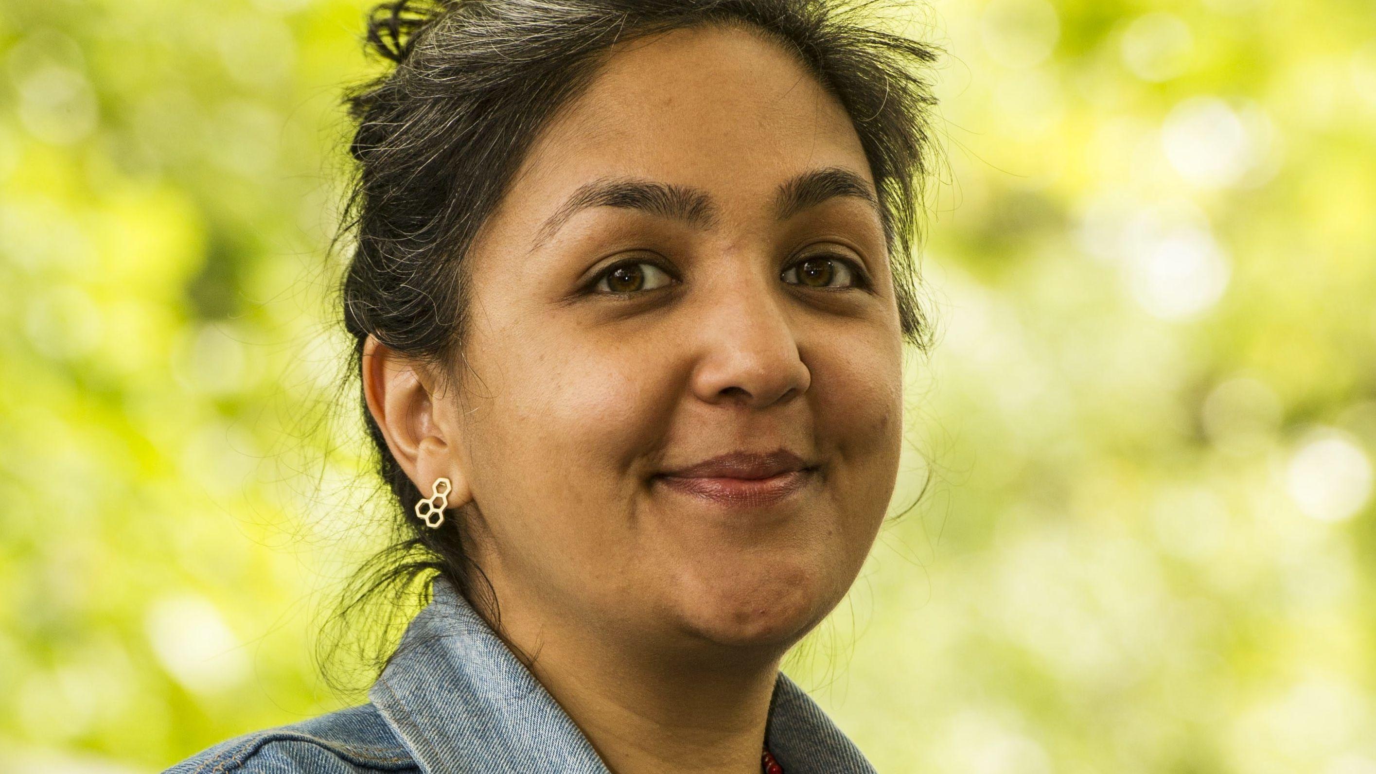 Autorin Preti Taneja blickt vor sonnenbeschienenem Laub lächelnd in die Kamera