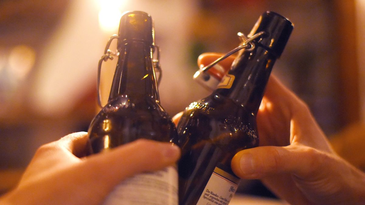Zwei Personen stoßen mit Bier an (Symbolfoto)