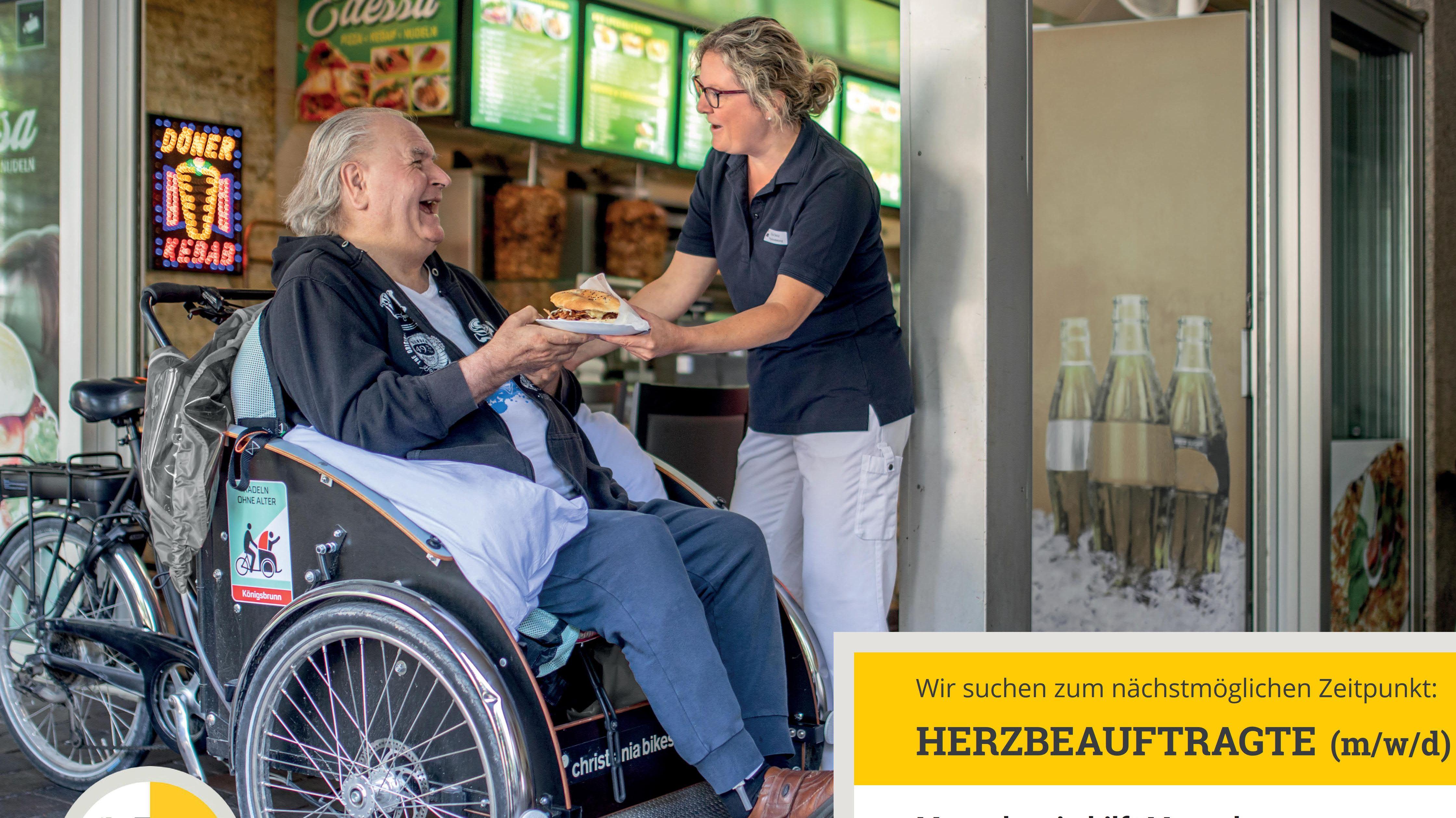 Ein Rollstuhlfahrer lacht glücklich eine Pflegerin an, die ihm einen Bürger reicht.