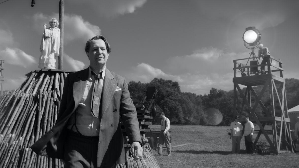 """Schwarzweißaufnahme: Ein Mann im Anzug geht zügig ins Bild - im Hintergrund Spots zum Drehen und Kulissen: Szenenfoto aus """"Mank"""""""