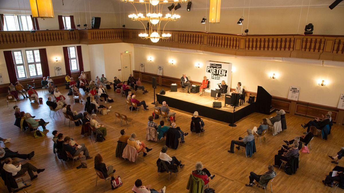Besucher sitzen in Abstand zueinander vor einer Bühne in einem Saal.