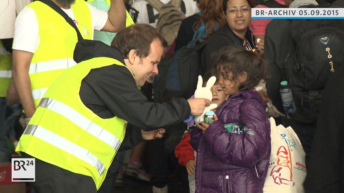 Ein Helfer überreicht einem Mädchen ein Stofftier