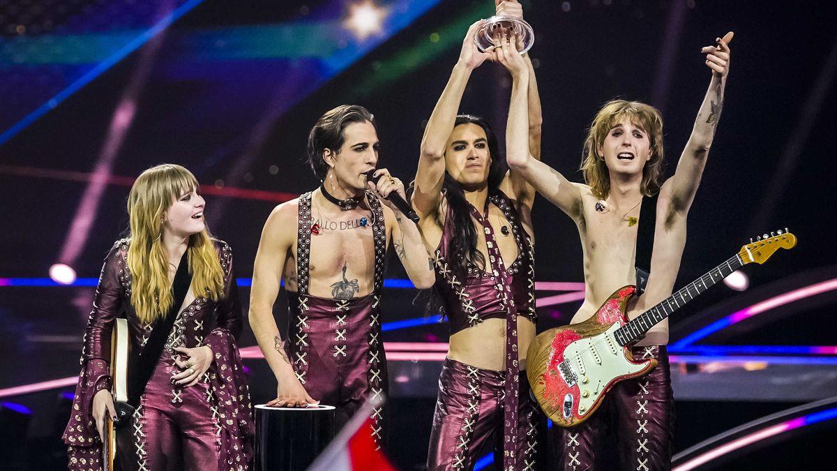 Die Bandmitglieder mit nackten Oberkörpern in weinroter Kluft
