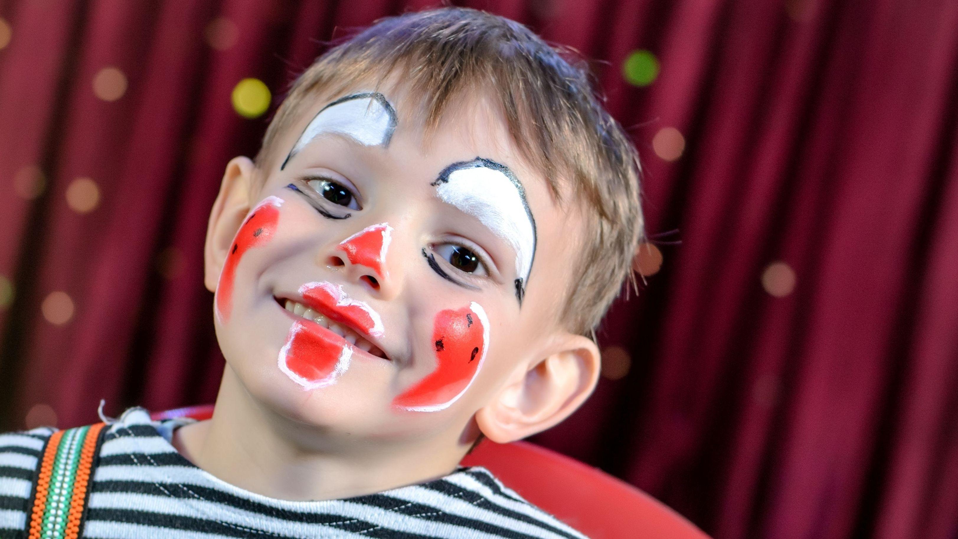 Als Clown geschminkter Junge