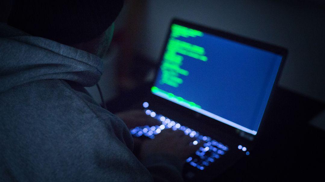 Ein Mann arbeitet an einem Laptop mit Programmcode auf dem Bildschirm.