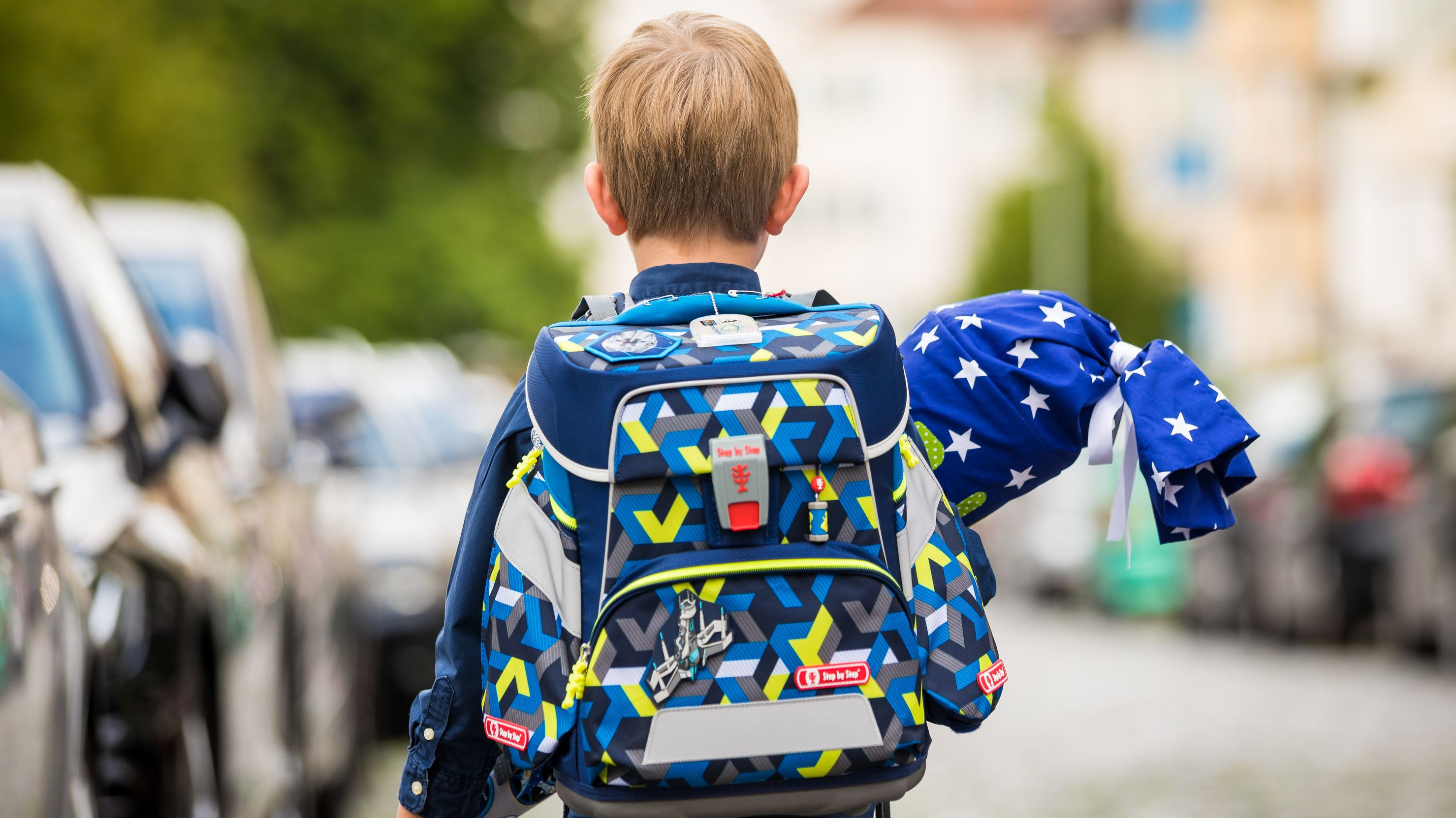 Kleiner Bub geht mit Schultüte und Schulranzen auf der Straße.