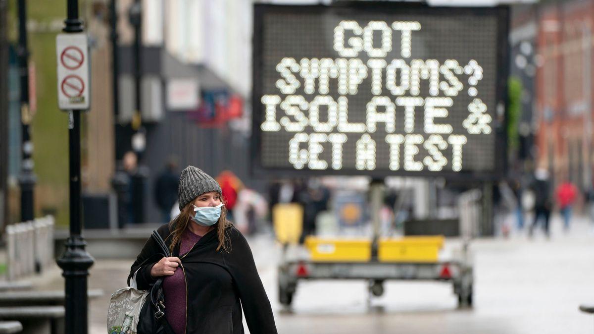 Eine Frau geht in Bolton, Großbritannien, an einem öffentlichen Informationsschild vorbei.